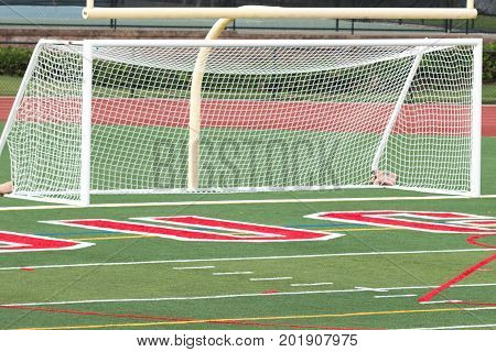 A new soccer goal on a new green turf field with red and white writing at a local high school.