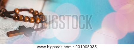 Digital composite of Rosary on bible and blue pink bokeh transition