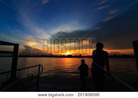 Sunset at port of Bangkok near riverside with people silhouette