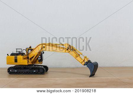 Crawler Excavator model on wooden floor with wall background