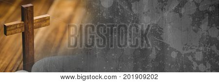 Digital composite of Wooden cross on bible and grey grunge cardboard transition