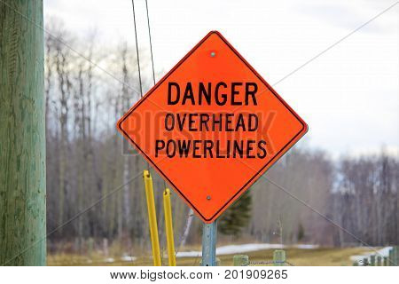 Danger Overhead Powerline Sign Beside A Power Pole