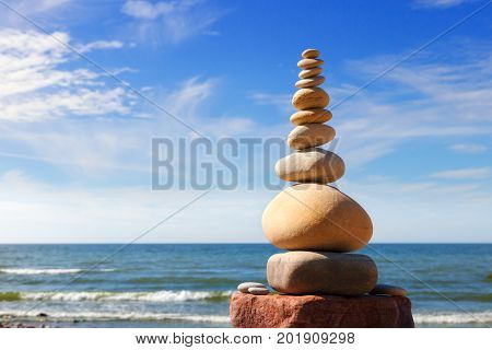 White round stones balance on a background of blue sky and sea. Concept of balance and harmony