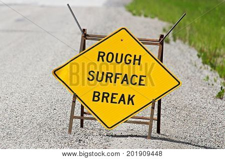 Closeup Of A Yellow Rough Surface Break Sign On Pavement
