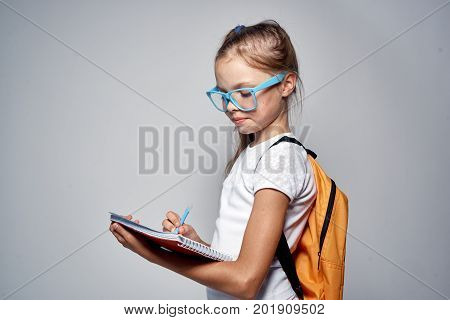little girl in blue glasses with a backpack.