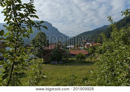 Scene with mountain top, forest, glade and residential district of bulgarian village Beli Iskar, Rila mountain, Bulgaria