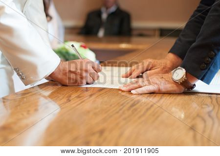 The groom signs his marriage at the town hall