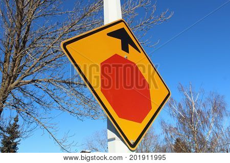 Stop Sign Ahead Against Blue Sky And Trees