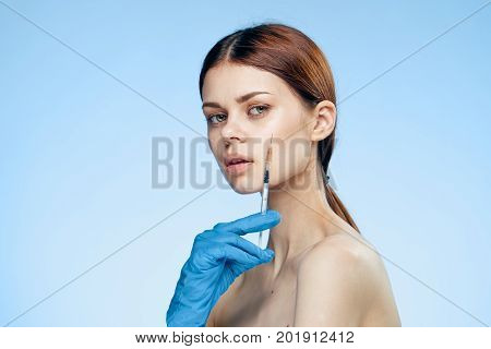 A woman in rubber gloves holds a syringe.