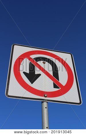 A No U-Turn Sign Against Blue Sky.