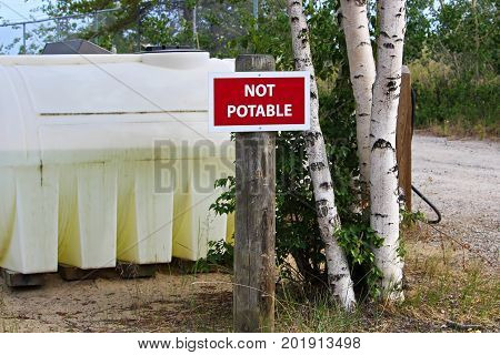 A not potable sign next to a water holding tank.