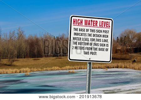 High Water Level Sign Along A Storm Drainage Pond