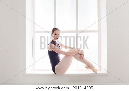 Young ballerina in black leotard sitting gracefully in a window case. Beautiful ballet dancer posing, side view, copy space