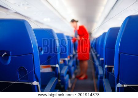 Passenger seat, Interior of airplane with passengers sitting on seats and stewardess walking the aisle in background. stewardess serves passengers. Service concept, Travel concept.