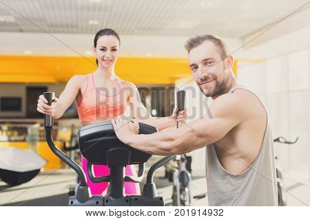 Couple in gym. Handsome guy helps young woman on elliptical trainer. Cardio workout in gym, healthy lifestyle