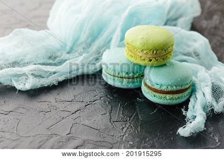 Classic French Macaroon cookies blue and green on black concrete background