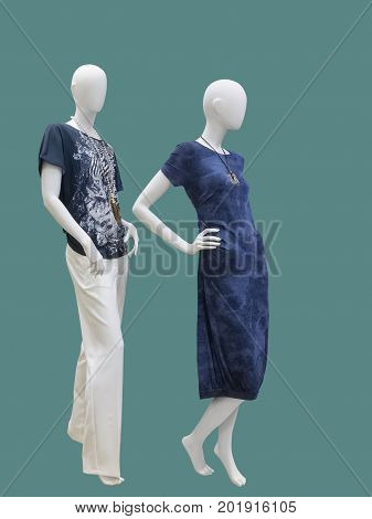 Two full-length female mannequins wear fashion clothing. Isolated on green background. No brand names or copyright objects.