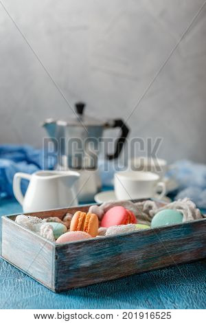 Classic French colorful mackerel cookies in wooden box cups for coffee and metal coffee maker on blue background