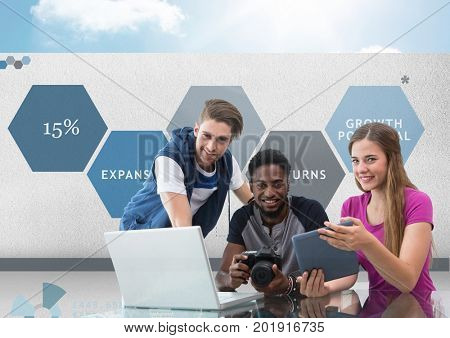 Digital composite of Group of young people on computer with camera in front of business graphics