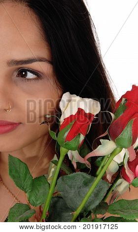 A beautiful woman with halve of her face and brunette hair holding a bunch of red and white roses isolated for white background