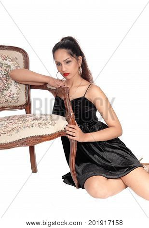 A unhappy young woman in a black dress sitting on the floor with her arm on an old armchair looking sad isolated for white background