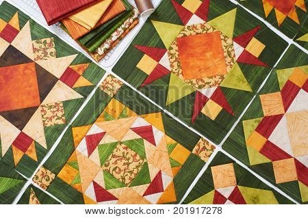 Assembling of quilt from orange-green, patchwork blocks, pile of fabric