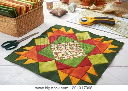 Patchwork orange-green block, quilting fabrics, sewing accessories