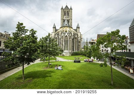 GHENT BELGIUM - JUNE 22 2016: Horizontal picture of the backside of Saint Nicholas' Church on a cloudy day with a garden with trees and people located in Ghent.