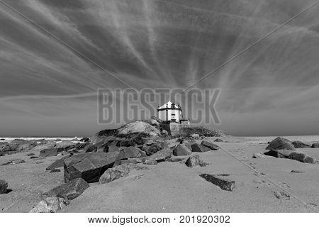 Miramar Beach and Chapel Senhor da Pedra, Atlantic ocean near Porto, Portugal.  Black-and-white photograph.