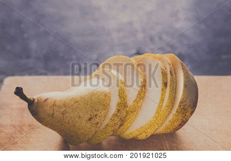 Sliced pear on wooden board background, selective focus, copy space, healthy food, diet and vegetarian concept