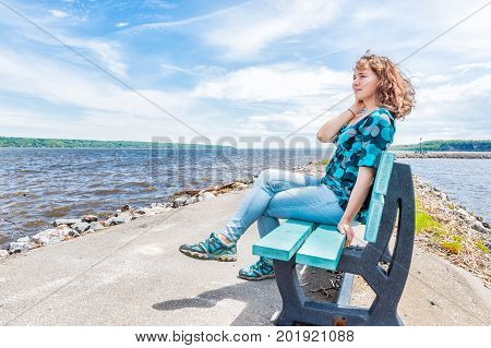 Young woman sitting on blue bench overlooking peaceful Saint Lawrence river in Portneuf Quebec Canada