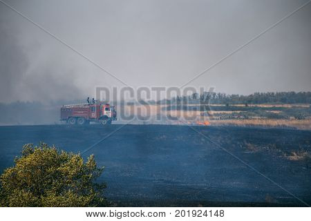 Rostov Region, Russia 20 AUGUST 2017: A car of firefighters or rescuers of the Emergencies Ministry extinguishes wildfires on the fields in the Rostov Region. Summer fires in the fields and forests