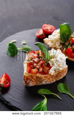 Italian appetizer on black slate background. Crusty bruschetta with concasse tomatoes, stracciatella cheese decorated with spinach. Delicious and healthy restaurant meals, copy space, closeup