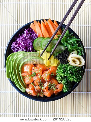 Healthy Japanese Salmon Poke Bowl with vegetables