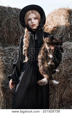 Fashion Young Woman Wearing Stylish Black Dress And Hat At Countryside. Amish Fashion Style.