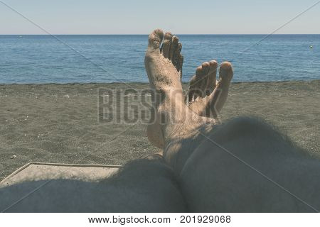 Male hairy legs tan in the sun overlooking the sea. the concept of relaxation leisure travel.