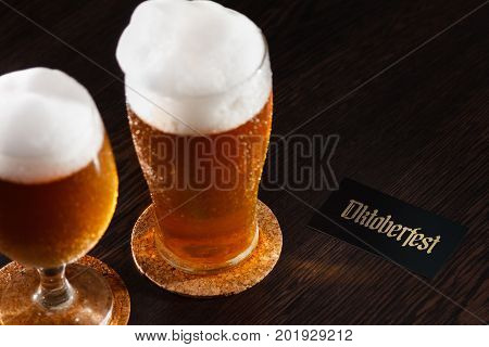 Beer glass pint on a wooden background with foam and Oktoberfest text. For a Bar or festival concept.