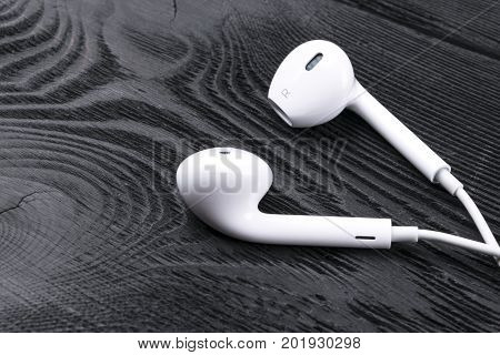 White little headphones on a black rustic wooden isolated background woodgrain texture