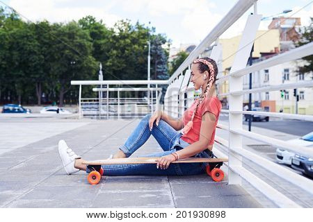 Wide shot of appealing woman relaxing while sitting under handrail with skateboard with copy space