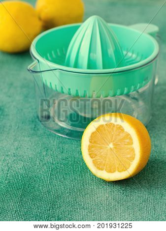 Fresh lemons with citrus squeezer on turquoise background. Copy space, vertical, toned