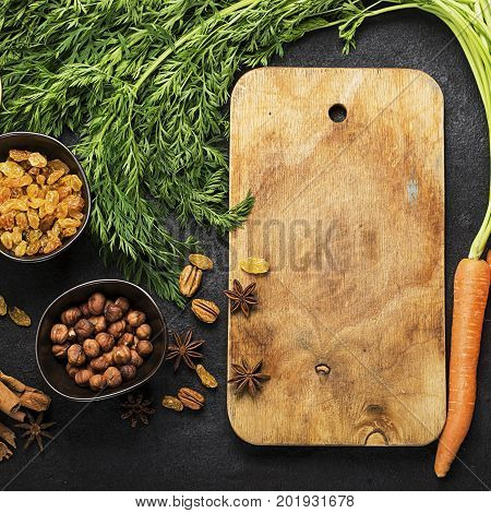 Ingredients for the traditional classic carrot flavored autumn seasonal pie: juicy fresh carrots, raisins, spices, spices, honey, nuts on a dark background. Top View