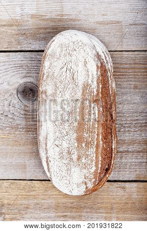 whole oval rye bread with baked flour on a crust on a wooden background