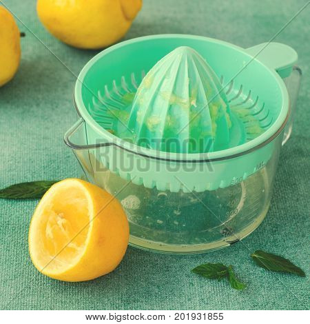 Fresh lemons and mint with citrus squeezer on turquoise background. Square, toned