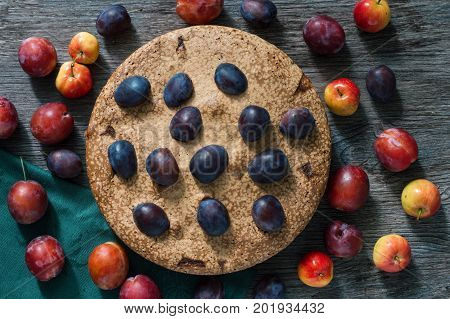 Pie with plum and apples. The cake on the wooden dark table is decorated with fresh plums and apples.View from above