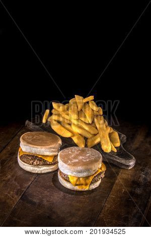Two mini delicious hamburgers with melted cheddar and fried potato on a dark wood background