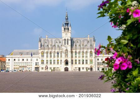 The market square and town hall of the Flemish town of Sint Niklaas in Belgium behind some flowers