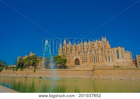 PALMA DE MALLORCA, SPAIN - AUGUST 18 2017: Beautiful view of Cathedral of Santa Maria of Palma La Seu in a gorgeous blue sky, with an artifical pond with a fountain in the middle, in Palma de Mallorca, Spain.