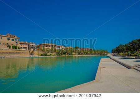 PALMA DE MALLORCA, SPAIN - AUGUST 18 2017: Beautiful view of Cathedral of Santa Maria of Palma La Seu in a gorgeous blue sky, with an artifical pond, in Palma de Mallorca, Spain.