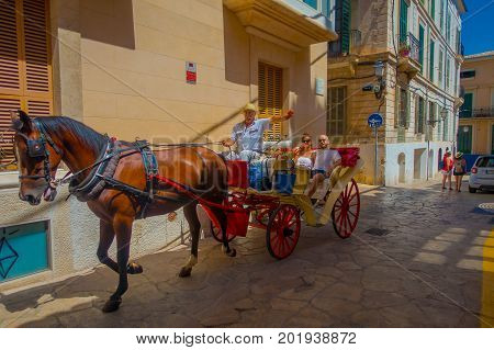 PALMA DE MALLORCA, SPAIN - AUGUST 18 2017: Unidentified couple over a carriage, traveling around the street in old city of Palma de Mallorca, Spain.