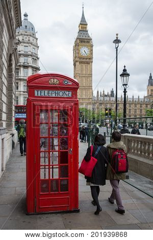 LONDON ENGLAND - JUNE 08 2017: People and call box at Parliament square near Big Ben in London UK